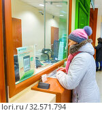 Russia, Samara, February 2017: a woman, a client of Sberbank of Russia, talking with the operator on the issue of financial transactions. The text in Russian: Sberbank, always near, the instruction for assessing the quality of service. Редакционное фото, фотограф Акиньшин Владимир / Фотобанк Лори