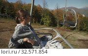 Smiling woman riding a cableway. Стоковое видео, видеограф Илья Шаматура / Фотобанк Лори