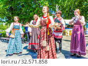 Russia, Samara, June 2017: smart girls in national clothes sing for city residents on the embankment of the Volga River on a sunny summer day. Редакционное фото, фотограф Акиньшин Владимир / Фотобанк Лори