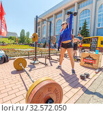 Купить «Russia, Samara, July 2017: a young beautiful woman lifts a weight at a sports festival on the Volga river embankment on a summer sunny day. The text in Russian: the strength of Crossfit sport.», фото № 32572050, снято 12 июня 2017 г. (c) Акиньшин Владимир / Фотобанк Лори