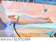 Russia, Samara, July 2017: A female doctor massage a woman lying down with a mechanical roller in the massage room on the embankment of the Volga River . Стоковое фото, фотограф Акиньшин Владимир / Фотобанк Лори