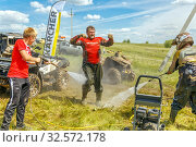 Купить «Russia, Samara, June 2017: washing a dirty ATV driver with water from a hose in the open air after an extreme run through mud in a summer sunny day.», фото № 32572178, снято 10 июня 2017 г. (c) Акиньшин Владимир / Фотобанк Лори