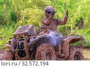Купить «Russia, Samara, June 2017: A dirty man on a dirty ATV shows his hands in a fan after an overcoming a heavy stretch of road.», фото № 32572194, снято 10 июня 2017 г. (c) Акиньшин Владимир / Фотобанк Лори