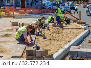 Купить «Russia, Samara, July 2017: working guest workers laying paving slabs in the city on the streets of the Young Guard in Sunny Summer Day.», фото № 32572234, снято 7 июля 2017 г. (c) Акиньшин Владимир / Фотобанк Лори