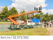 Russia, Samara, June 2017: repair and restoration of a street pillar on the street of old-sunbath on a summer sunny day. Text in Russian: stop. Редакционное фото, фотограф Акиньшин Владимир / Фотобанк Лори