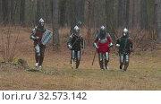 Купить «Four men knightes running in the row in the forest in full armour holding weapons», видеоролик № 32573142, снято 8 июля 2020 г. (c) Константин Шишкин / Фотобанк Лори