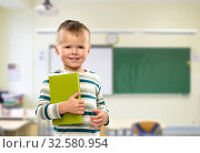 Купить «portrait of smiling boy holding book at school», фото № 32580954, снято 28 сентября 2019 г. (c) Syda Productions / Фотобанк Лори