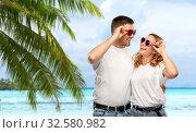 Купить «happy couple in white t-shirts and sunglasses», фото № 32580982, снято 6 октября 2019 г. (c) Syda Productions / Фотобанк Лори