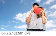Купить «smiling couple hiding behind big red heart», фото № 32581078, снято 6 октября 2019 г. (c) Syda Productions / Фотобанк Лори
