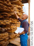 Купить «Carpenter in uniform check boards on sawmill», фото № 32587726, снято 19 сентября 2019 г. (c) Tryapitsyn Sergiy / Фотобанк Лори