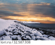 Купить «Arctic ocean with stones covered with ice and mountains on the horizon at sunset», фото № 32587938, снято 7 марта 2016 г. (c) Наталья Волкова / Фотобанк Лори