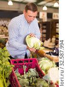 Купить «Man choosing cauliflower in supermarket», фото № 32587994, снято 9 октября 2019 г. (c) Яков Филимонов / Фотобанк Лори