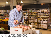 Купить «Man choosing onion in supermarket», фото № 32588002, снято 9 октября 2019 г. (c) Яков Филимонов / Фотобанк Лори
