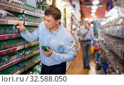 Adult man buyer selects parts for electricians. Стоковое фото, фотограф Яков Филимонов / Фотобанк Лори