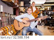 Купить «Boy and father choosing acoustic guitar», фото № 32588194, снято 29 марта 2017 г. (c) Яков Филимонов / Фотобанк Лори