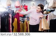Купить «Woman choosing colorful blouse», фото № 32588306, снято 7 февраля 2017 г. (c) Яков Филимонов / Фотобанк Лори