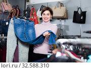 Купить «Happy girl deciding on new jeans», фото № 32588310, снято 7 февраля 2017 г. (c) Яков Филимонов / Фотобанк Лори