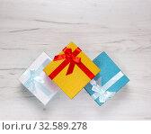 Купить «Три праздничных ярких коробки с бантами и лентами на деревянном фоне», фото № 32589278, снято 29 ноября 2019 г. (c) Sergei Gorin / Фотобанк Лори