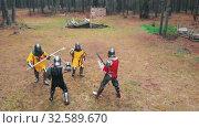 Купить «Four men knightes having a training fight on the field in the forest using swords», видеоролик № 32589670, снято 27 мая 2020 г. (c) Константин Шишкин / Фотобанк Лори