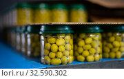 Rows of glass jars of green olives in brine. Стоковое фото, фотограф Яков Филимонов / Фотобанк Лори