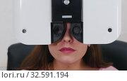 Купить «Ophthalmology treatment - a young woman with bright pink lips checking her visual acuity with a special optometry equipment - talking while her eyes are closed with a machine», видеоролик № 32591194, снято 24 февраля 2020 г. (c) Константин Шишкин / Фотобанк Лори