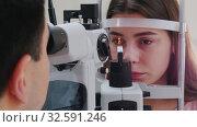 Купить «Ophthalmology treatment - a young woman with pink lips checking her visual acuity - pupil reaction to light», видеоролик № 32591246, снято 20 февраля 2020 г. (c) Константин Шишкин / Фотобанк Лори