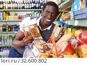 Купить «African man choosing pasta», фото № 32600802, снято 7 ноября 2018 г. (c) Яков Филимонов / Фотобанк Лори