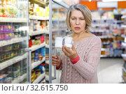 Купить «Amazed mature woman reading contents of products», фото № 32615750, снято 8 февраля 2019 г. (c) Яков Филимонов / Фотобанк Лори