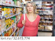 Купить «Thoughtful mature woman among shelves in grocery shop», фото № 32615774, снято 8 февраля 2019 г. (c) Яков Филимонов / Фотобанк Лори