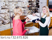 Купить «Seller displaying various fabrics», фото № 32615826, снято 15 февраля 2017 г. (c) Яков Филимонов / Фотобанк Лори