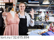 Woman sewer standing near mannequin with new dress at sewing workshop. Стоковое фото, фотограф Яков Филимонов / Фотобанк Лори