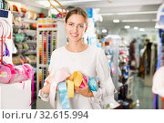 Portrait of delighted young woman with colorful ribbons for sewing in haberdasher shop. Стоковое фото, фотограф Яков Филимонов / Фотобанк Лори