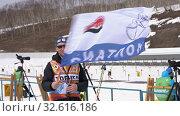 Купить «Biathlon team coach waving sports flag with emblem Kamchatsky Territory, logo Kamchatka Biathlon Federation. Junior biathlon competitions East of Cup», видеоролик № 32616186, снято 13 апреля 2019 г. (c) А. А. Пирагис / Фотобанк Лори
