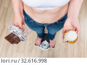 woman weighs on scales, chocolate in her hands and donut. Стоковое фото, фотограф Константин Лабунский / Фотобанк Лори