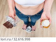 Купить «woman weighs on scales, chocolate in her hands and donut», фото № 32616998, снято 24 июня 2017 г. (c) Константин Лабунский / Фотобанк Лори