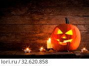 Купить «Halloween pumpkin head jack o lantern and candles on wooden background», фото № 32620858, снято 31 марта 2020 г. (c) easy Fotostock / Фотобанк Лори