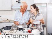 Купить «Woman and father discussing instructions for mixer tap», фото № 32627794, снято 19 июня 2018 г. (c) Яков Филимонов / Фотобанк Лори