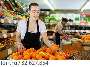 Купить «Young woman wearing apron working with fresh oranges», фото № 32627854, снято 27 апреля 2019 г. (c) Яков Филимонов / Фотобанк Лори