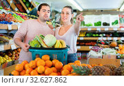 Купить «Positive family couple standing with full cart after shopping and pointing to shelves in fruit store», фото № 32627862, снято 27 апреля 2019 г. (c) Яков Филимонов / Фотобанк Лори