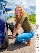 Young european woman changing car tire on rural road. Стоковое фото, фотограф Zoonar.com/Ben Schonewille / easy Fotostock / Фотобанк Лори