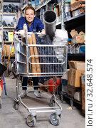Young woman in uniform walking during shopping construction materials with basket in build shop. Стоковое фото, фотограф Яков Филимонов / Фотобанк Лори