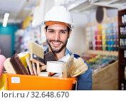 Купить «Workman holding basket with picked tools in paint store», фото № 32648670, снято 13 сентября 2017 г. (c) Яков Филимонов / Фотобанк Лори
