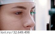 Купить «Ophthalmology treatment - a young woman checking her visual acuity - checking a reaction on the green light», видеоролик № 32649498, снято 20 февраля 2020 г. (c) Константин Шишкин / Фотобанк Лори