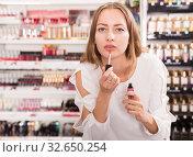 Woman choosing lip gloss. Стоковое фото, фотограф Яков Филимонов / Фотобанк Лори