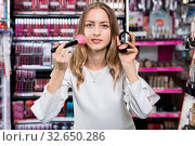 Купить «Young cheerful woman applying blush with makeup brush in cosmetics store», фото № 32650286, снято 19 октября 2019 г. (c) Яков Филимонов / Фотобанк Лори
