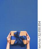 Female hands hold gift box on blue 2020 color. Стоковое фото, фотограф Ольга Сергеева / Фотобанк Лори