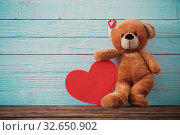 Купить «Teddy bear with red heart on old wooden background. Valentine's day concept», фото № 32650902, снято 14 декабря 2019 г. (c) Майя Крученкова / Фотобанк Лори