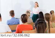 Купить «Young female teacher lecturing to students», фото № 32696062, снято 31 марта 2020 г. (c) Яков Филимонов / Фотобанк Лори