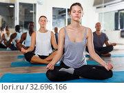Купить «Woman practicing yoga in group», фото № 32696166, снято 30 июля 2018 г. (c) Яков Филимонов / Фотобанк Лори