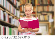 Купить «smiling little girl reading book at library», фото № 32697010, снято 28 сентября 2019 г. (c) Syda Productions / Фотобанк Лори
